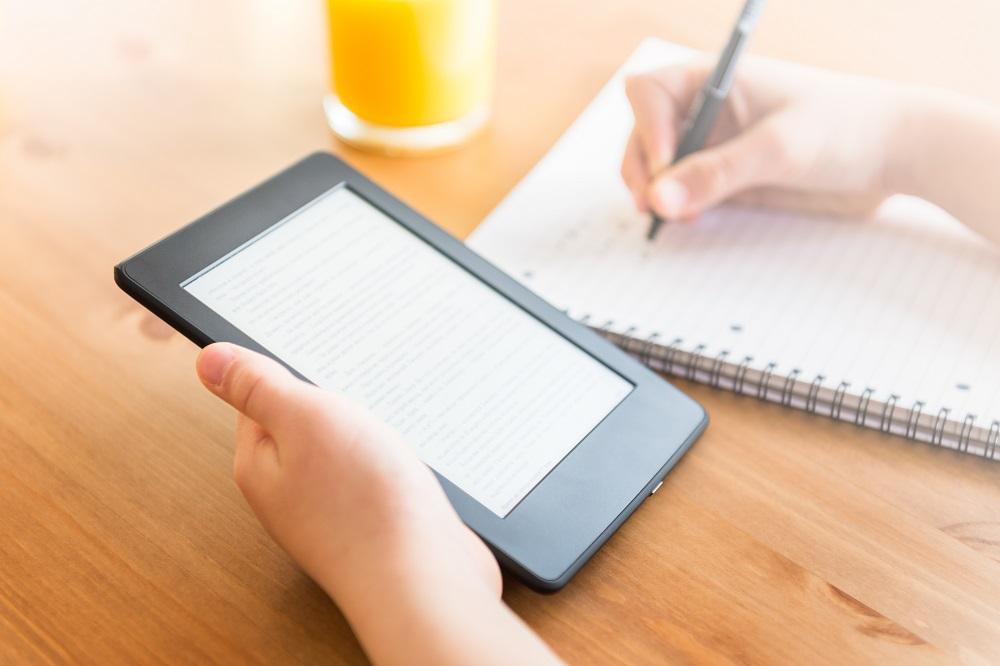 pessoa fazendo anotação sobre um livro digital