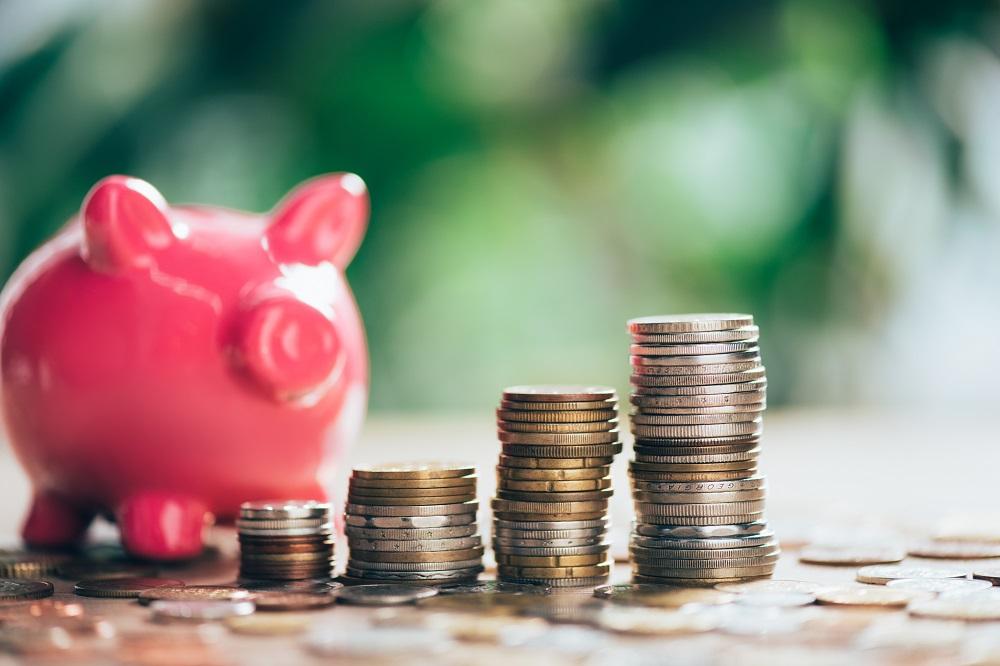 porco cofre com moedas ao redor