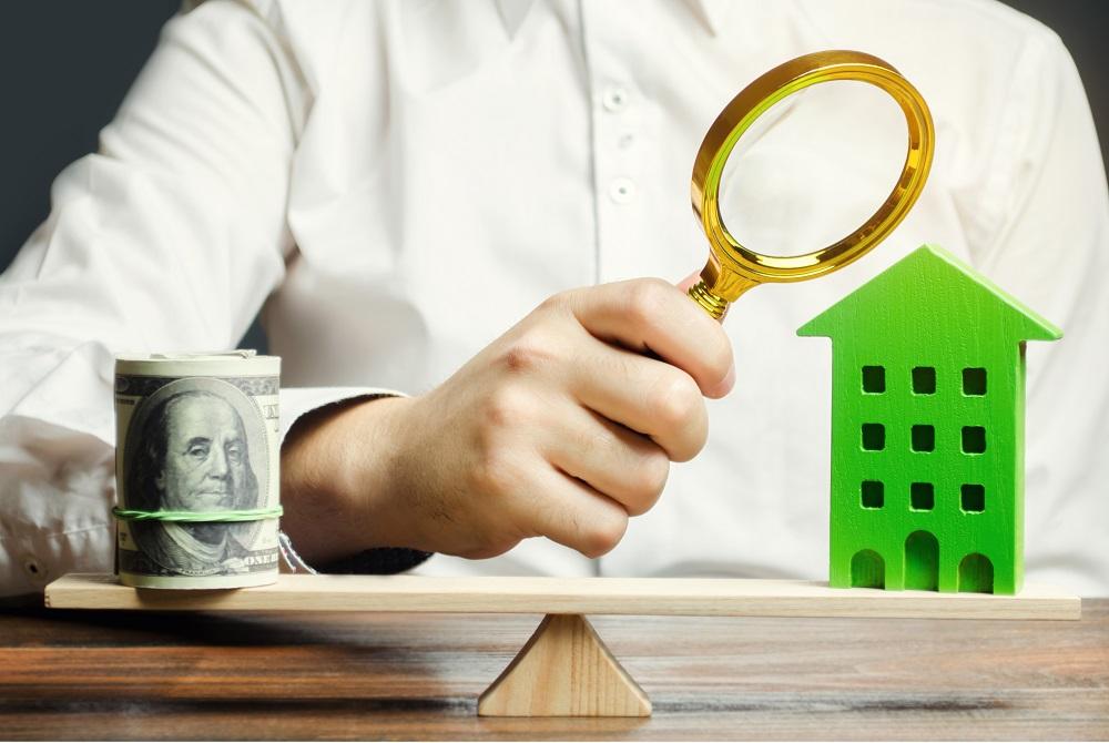 investidor com uma lupa analisando uma balança entre um imóvel e um montante de dinheiro