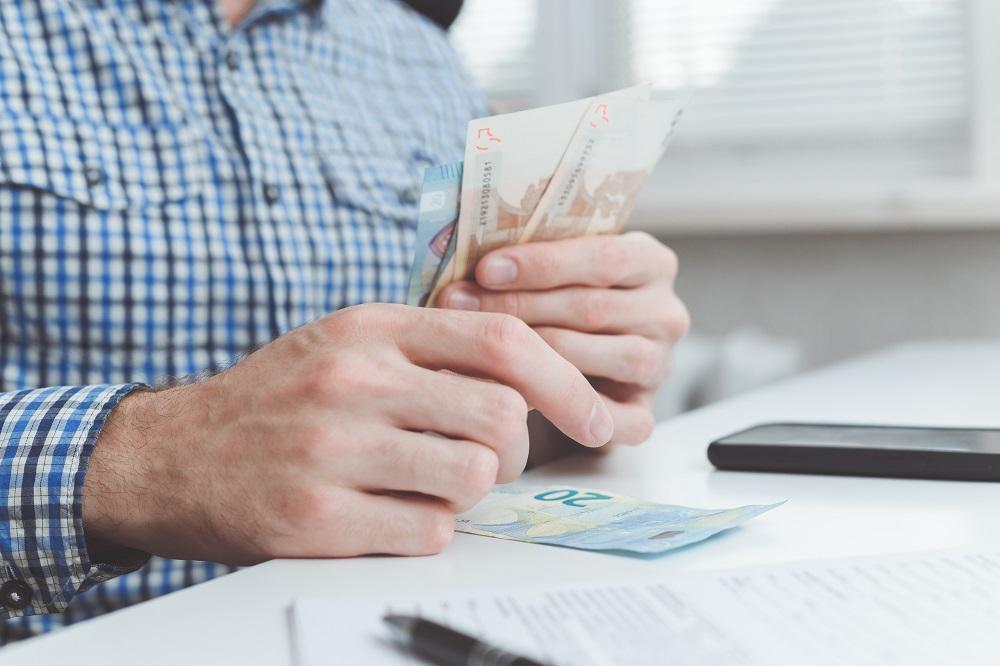 homem com dinheiro em mãos perto de uma calculadora