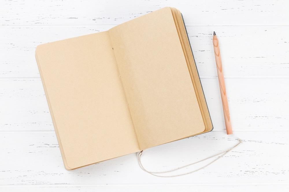 caderno de anotação e lápis