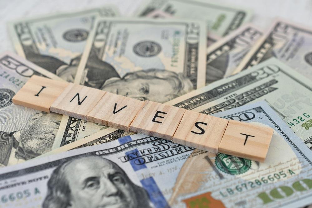 bloco de letras escrito investimento em cima de uma quantia em dinheiro