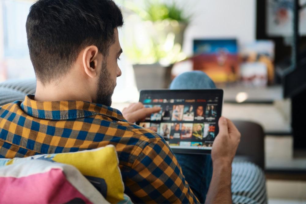 homem selecionando no tablet um filme para assistir