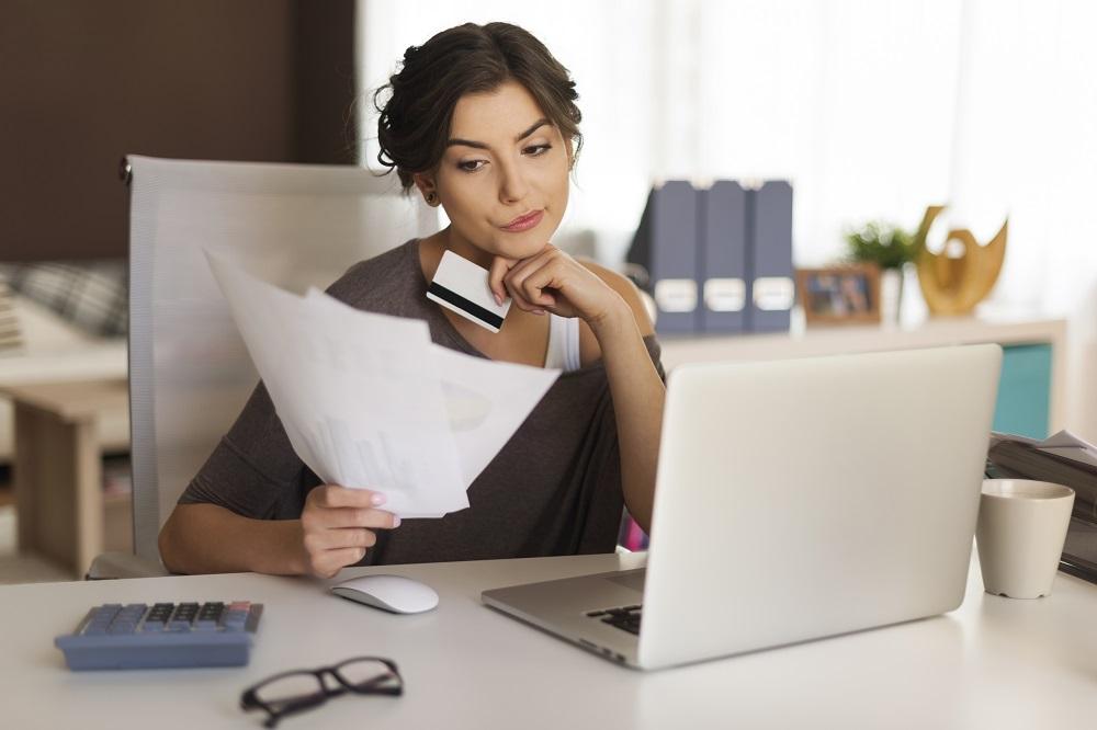 mulher pensativa olhando contas para pagar