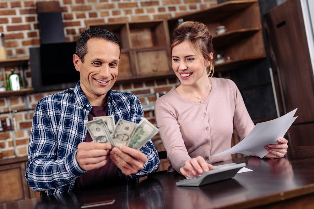 casal sorrindo ao acompanhar suas finanças