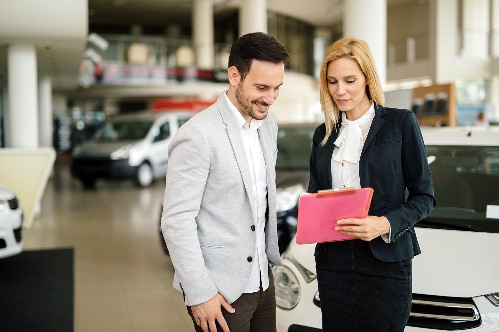 mulher de negócios mostrando carta de consórcio de veículos a um homem em uma consecionária