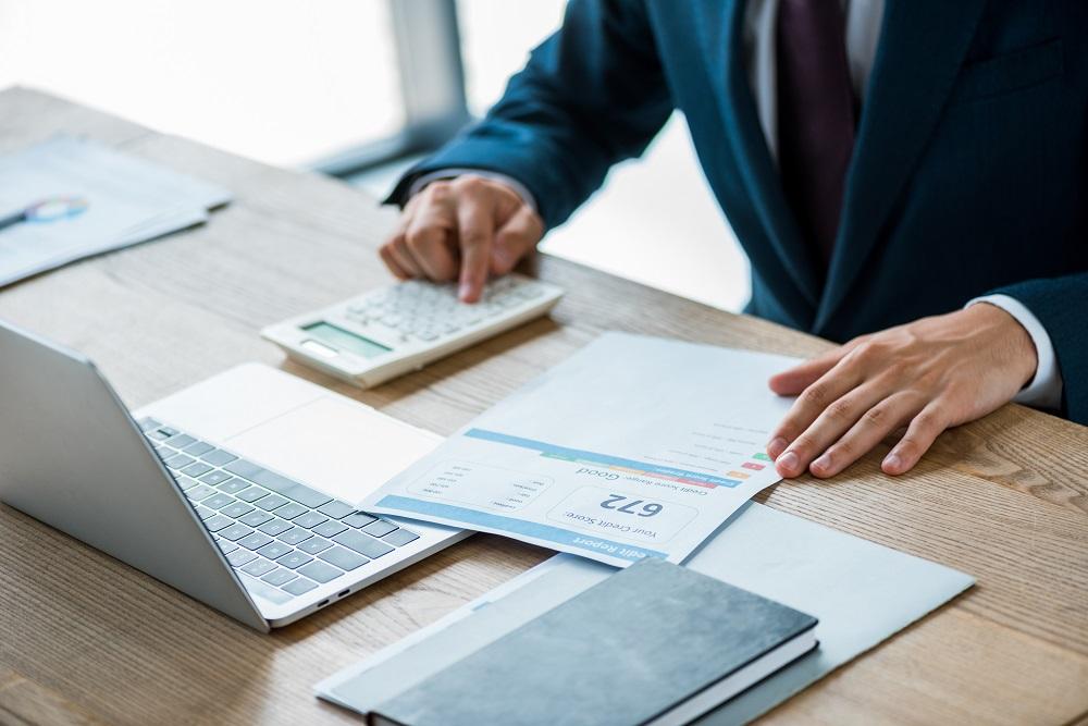 homem segurando o papel com rotulação de relatório de crédito e contando com a calculadora