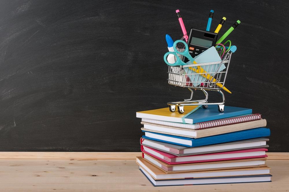 imagem de um carrinho de compras cheio de material escolar em cima de uma pilha de livros e cadernos