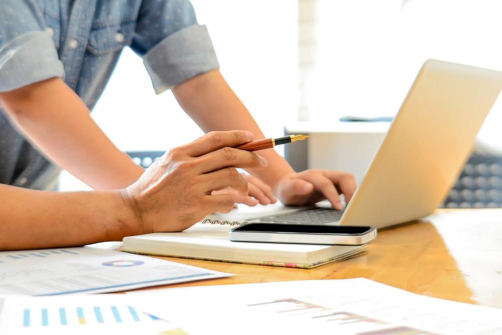 mão de um homem mexendo no computador, rodeado de papéis de investimento