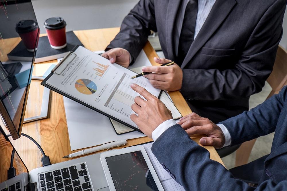 dois investidores analisando uma planilha de resultados