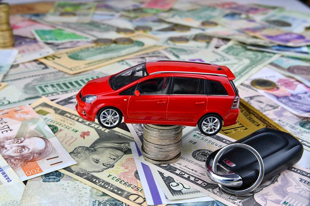 carro de brinquedo sobre uma pilha de moedas e rodeado de dinheiro