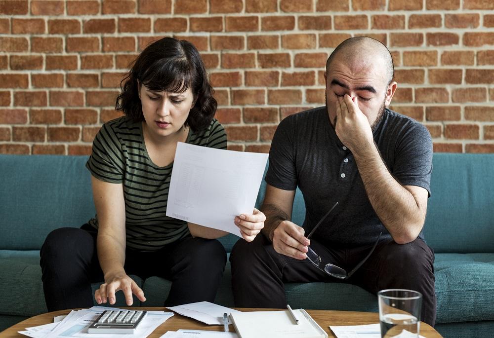 casal analisando as finanças e com semblante preocupado