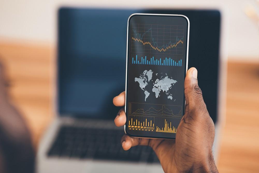 mão segurando celular mostrando resultados de ações