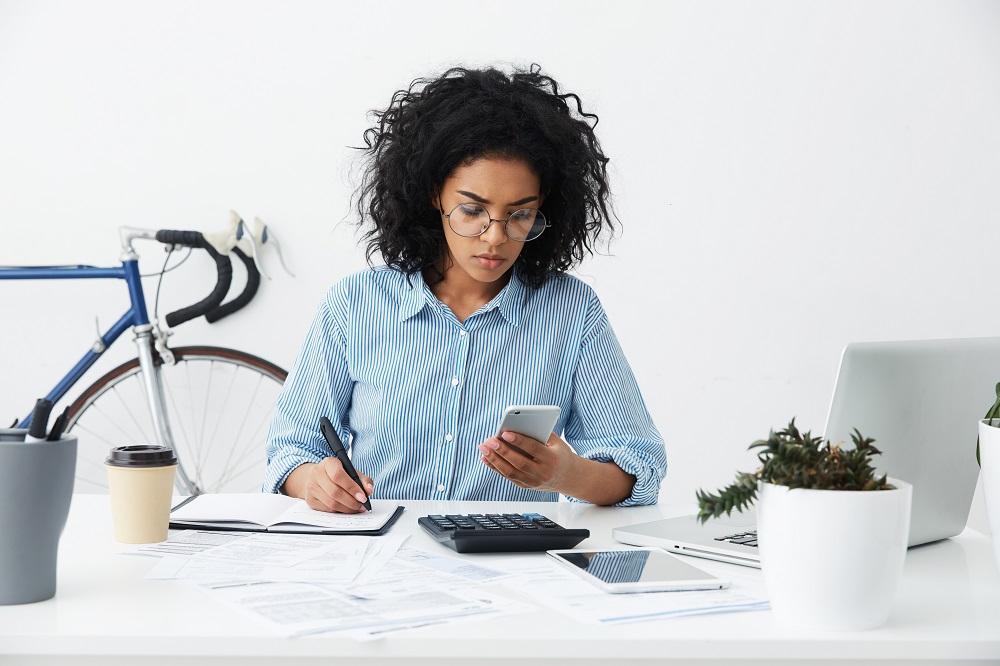 mulher sentada em uma mesa de escritório anotando e calculando