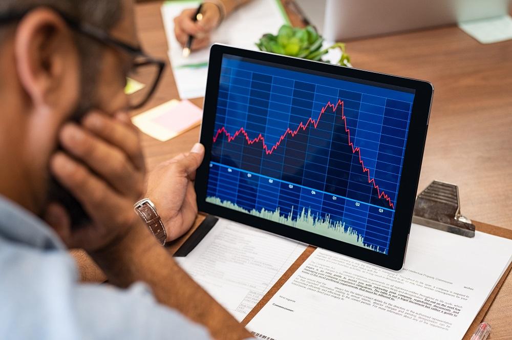 homem analisando gráfico de compra e venda de ações no tablet e ao lado documentos