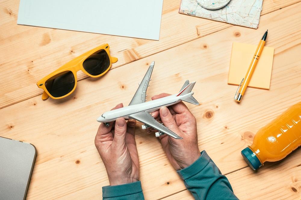 mão de um homem segurando um avião de brinquedo rodeado de itens de viagem
