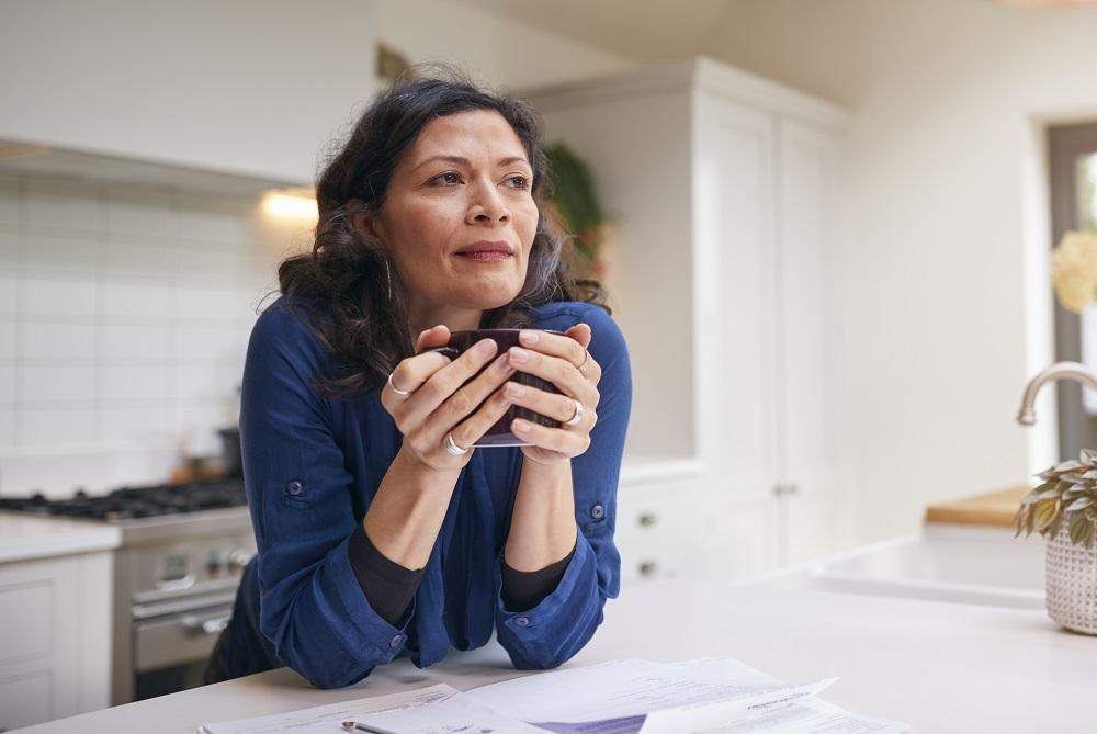 mulher segurando uma xícara e pensando sobre suas finanças