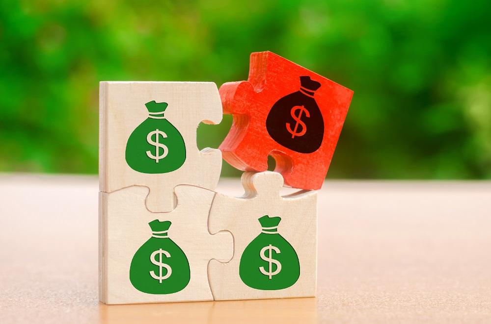 quatro blocos de madeira com símbolo de dinheiro, um deles em vermelho mostrando algo negativo