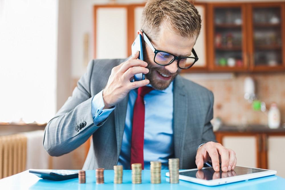 homem de negócios no telefone e mexendo em um tablet, e a sua frente uma pilha crescente de moedas