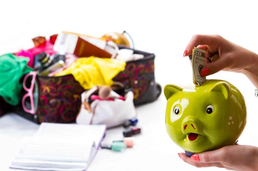 mão de mulher colocando dinheiro em um cofrinho de porco verde e ao fundo uma mala com itens para viajar