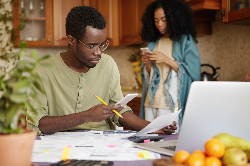 homem sentado na mesa da cozinha rodeado de papéis, mexendo no notbook e a esposa ao fundo mexendo no celular