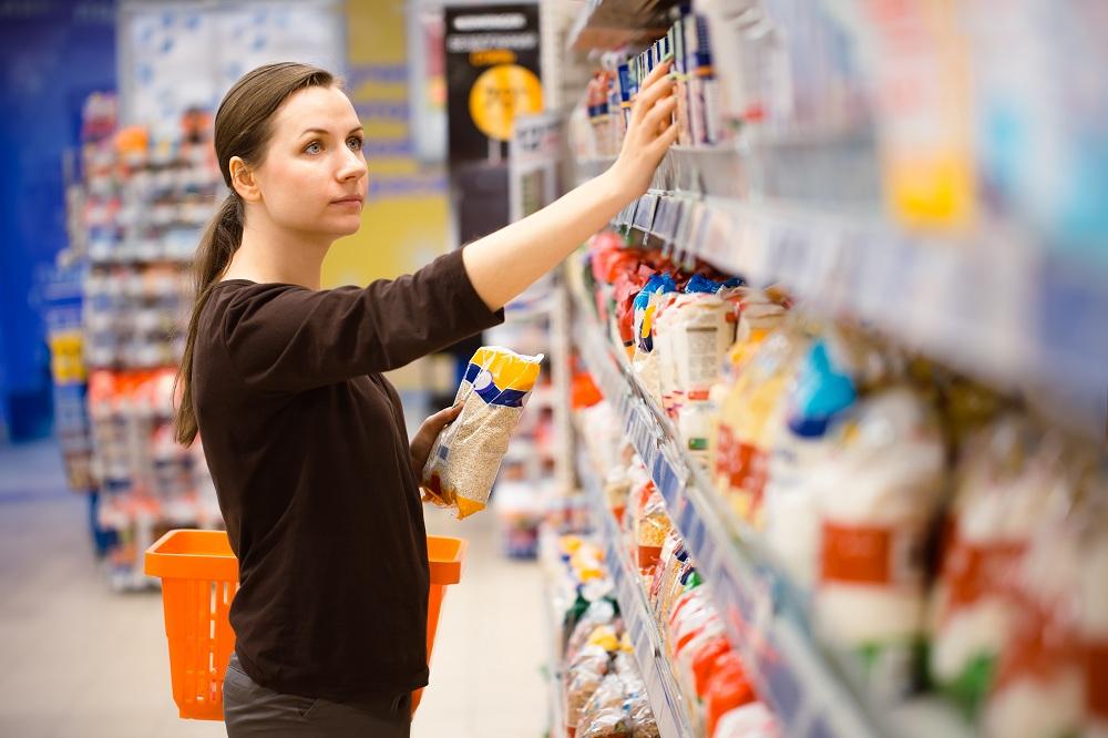 mulher comparando marca de arroz na prateleira do supermercado