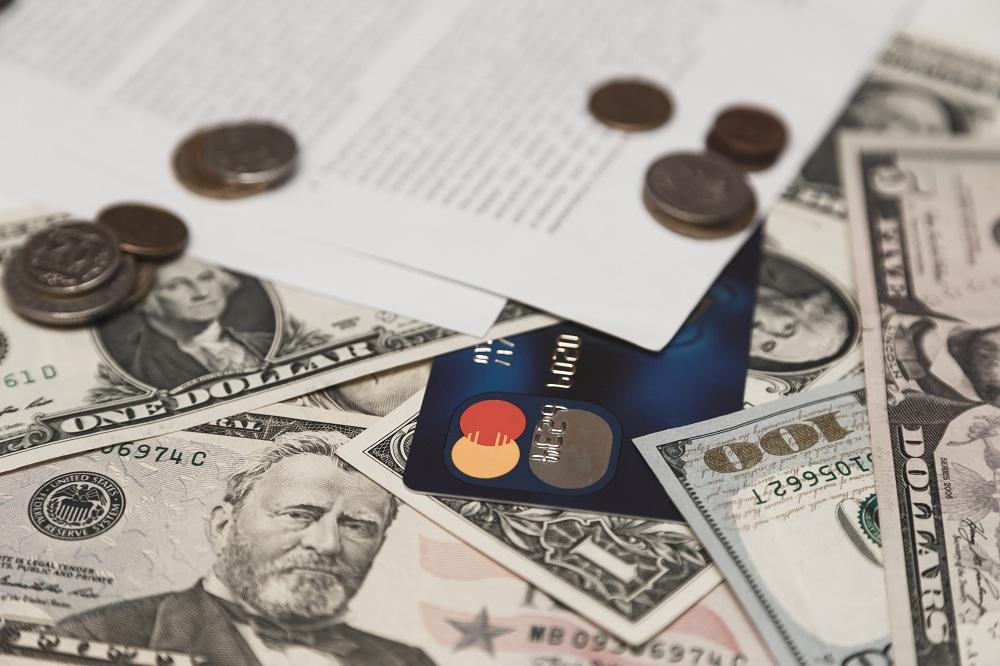 cartão de crédito em cima de notas de dinheiro e moedas