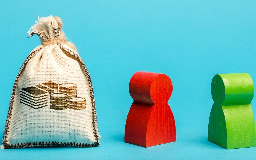 saco de moedas ao lado de dois bonecos de madeira