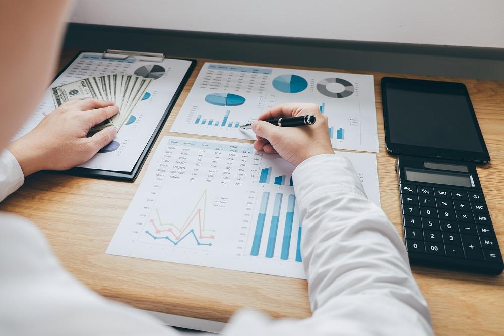 mão de homem analisando gráficos ao lado de dinheiro e calculadora