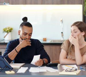 casal em choque olhando suas dívidas