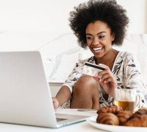 mulher morena fazendo compras online com seu cartão de crédito, com muita felicidade