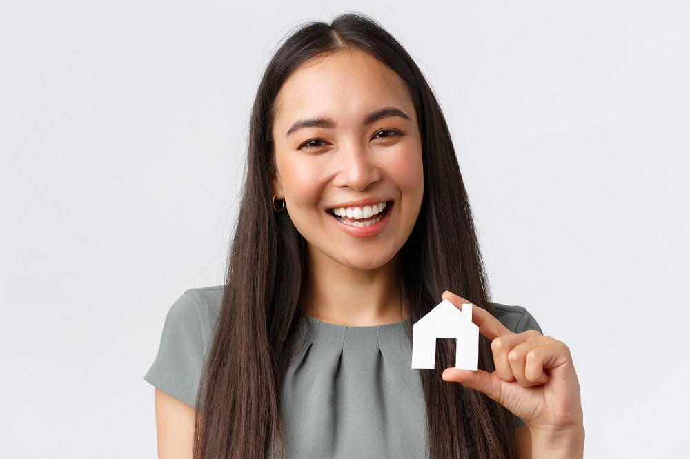 mulher sorridente com uma miniatura de casa na mão