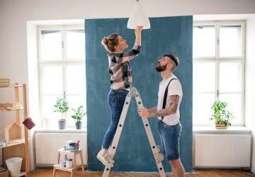 Casal de adultos meados mudando a lâmpada dentro de casa em casa