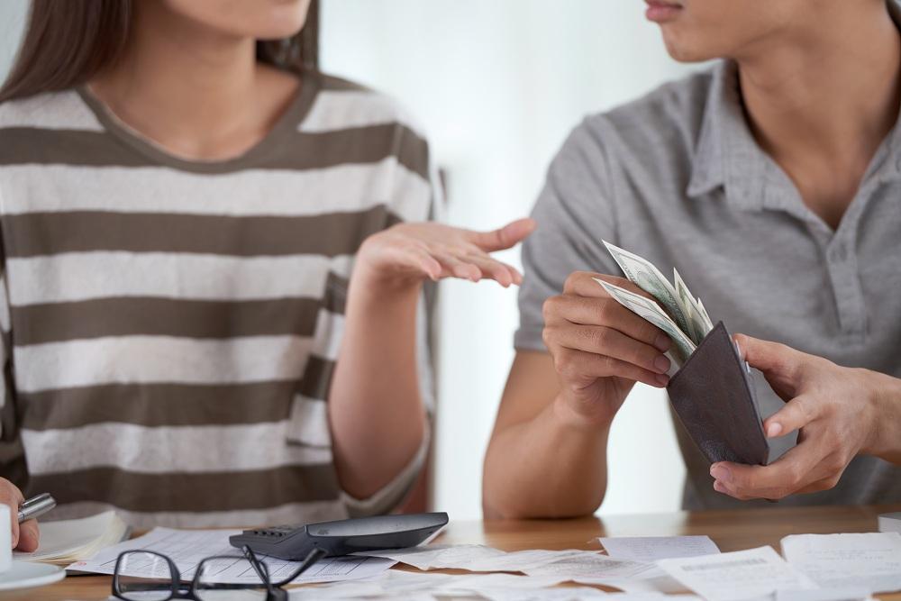 casal organizando as finanças, ele com dinheiro ela com calculadora