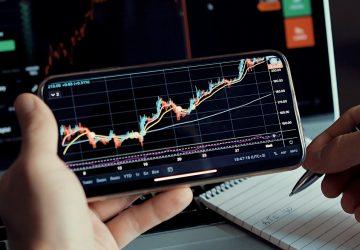 homem olhando mercado de ações no celular e fazendo anotações