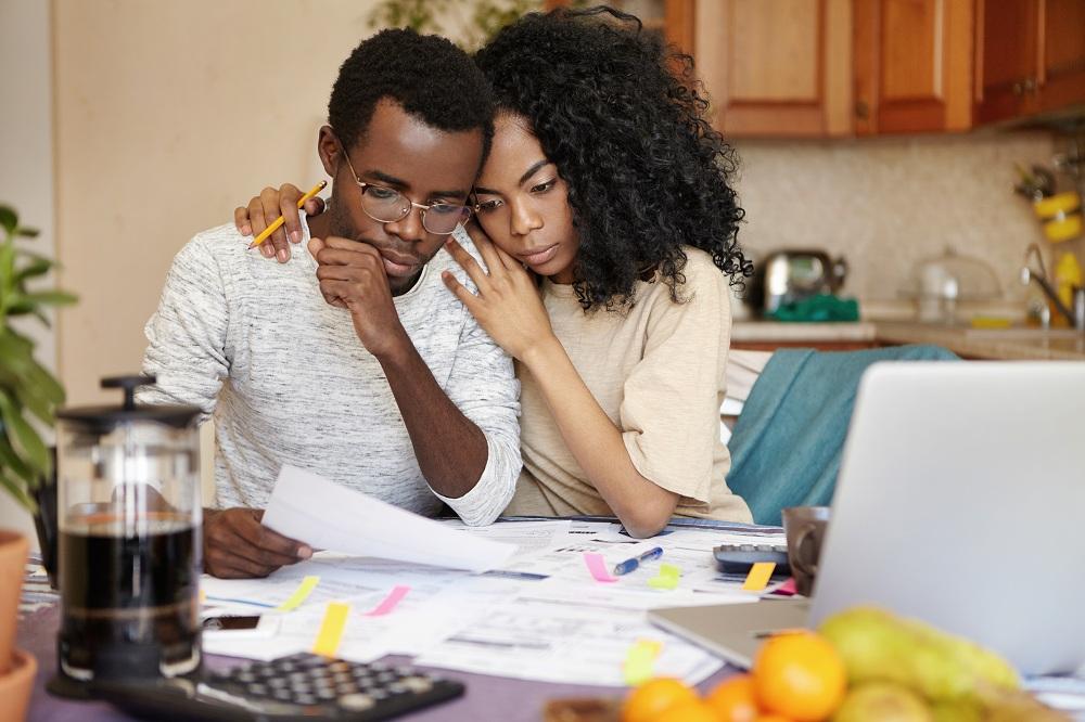 Família jovem africana em crise financeira. Mulher bonita abraçando seu marido