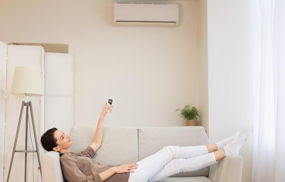 mulher jovem ligando no ar condicionado em sua casa