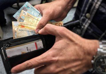 carteira mostrando homem colocando dinheiro ao antecipar o 13° salário