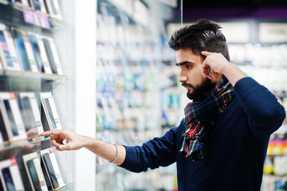 homem na loja de eletrônicos vendo como comprar celular barato