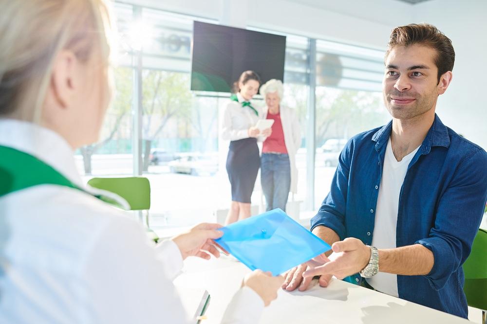 Homem recebendo documentos do representante do banco na hora de ter crédito aprovado