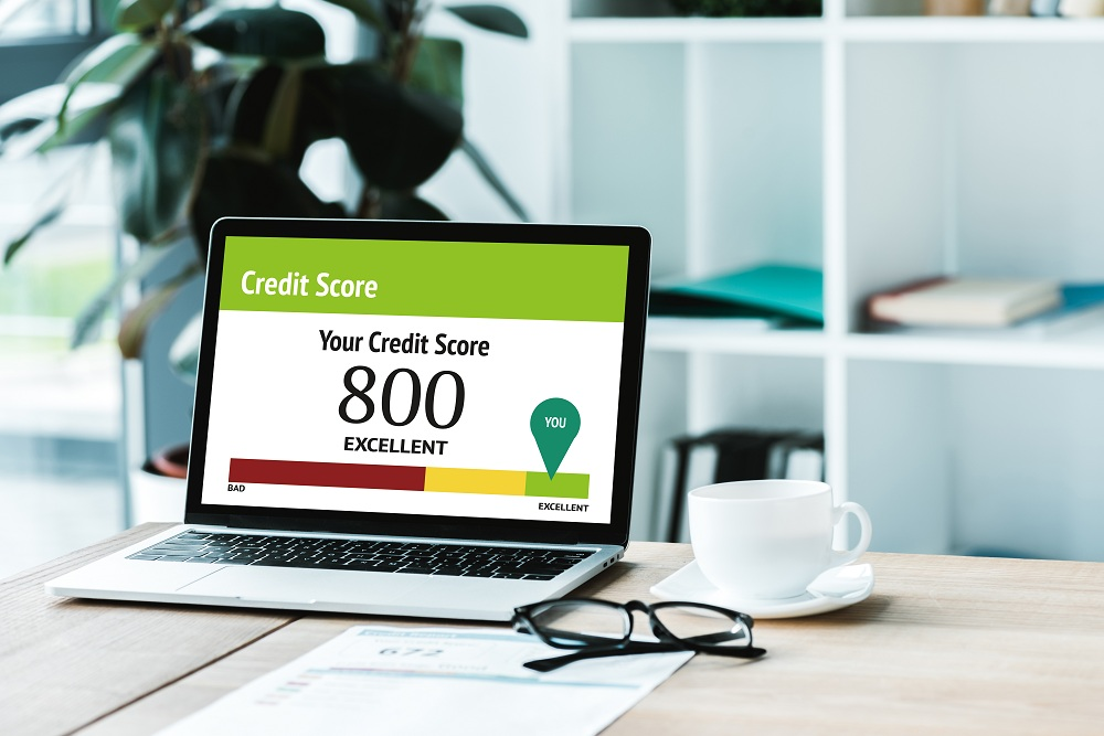xícara de café perto de laptop com rotulação de score de crédito em 800 pontos
