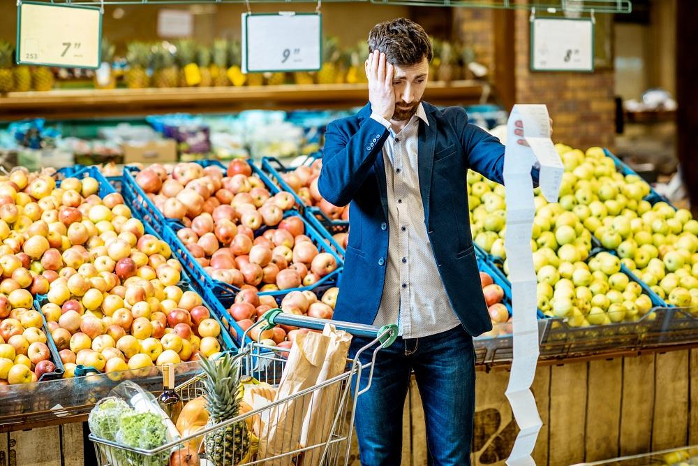 Homem com lista de compras no supermercado com aspecto assustado devido ao alto preço da cesta básica