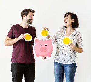 casal segurando um cofre de porco rosa inserindo moedas de papel simbolizando a perca do medo de como investir sem perder dinheiro
