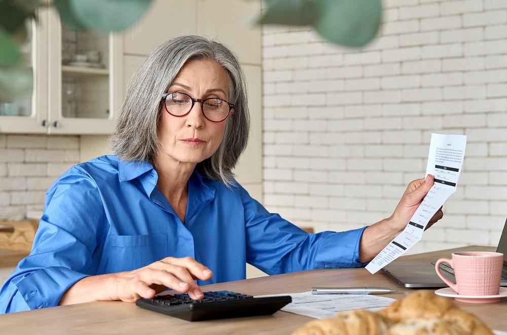 mulher idosa calculando as tarifas mostradas em um papel de banco digital ou tradicional