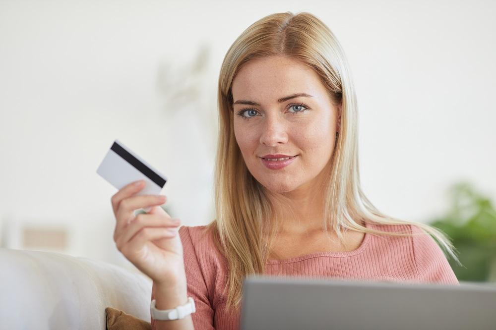 Mulher segurando um cartão, simbolizando como funciona o cartão de crédito