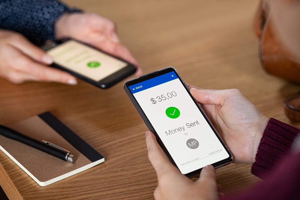 Mulher enviando dinheiro com telefone simulando um pagamento via PIX