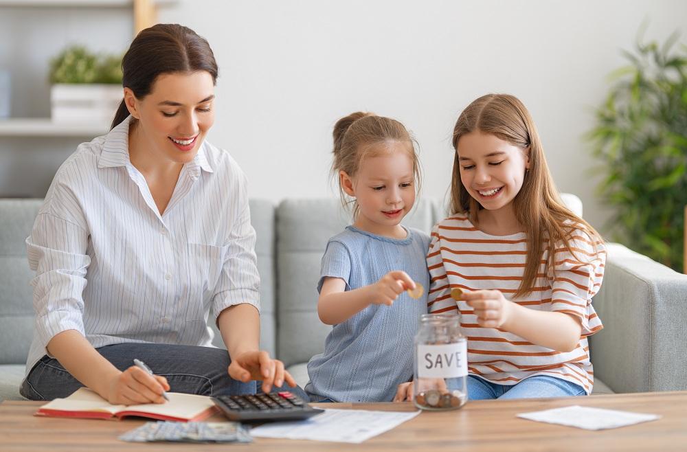 família feliz (mãe e duas filhas) fazendo contas e guardando dinheiro, simbolizando uma vida financeira estável