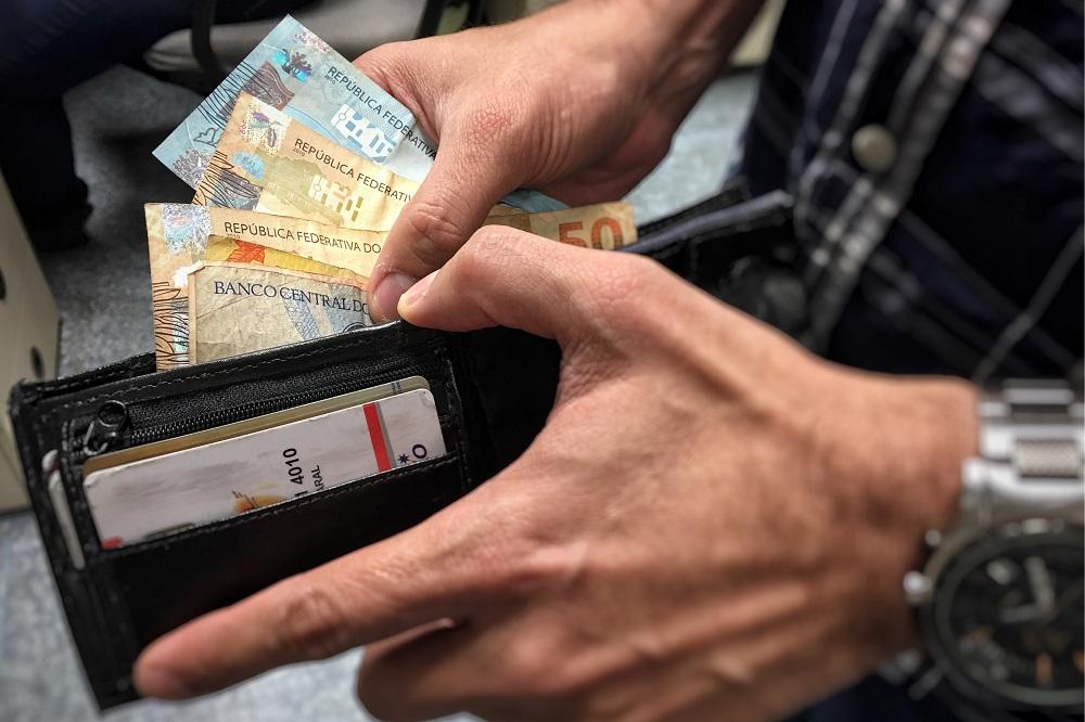 homem colocando dinheiro dentro da carteira, simbolizando o pagamento da restituição do IR 2021