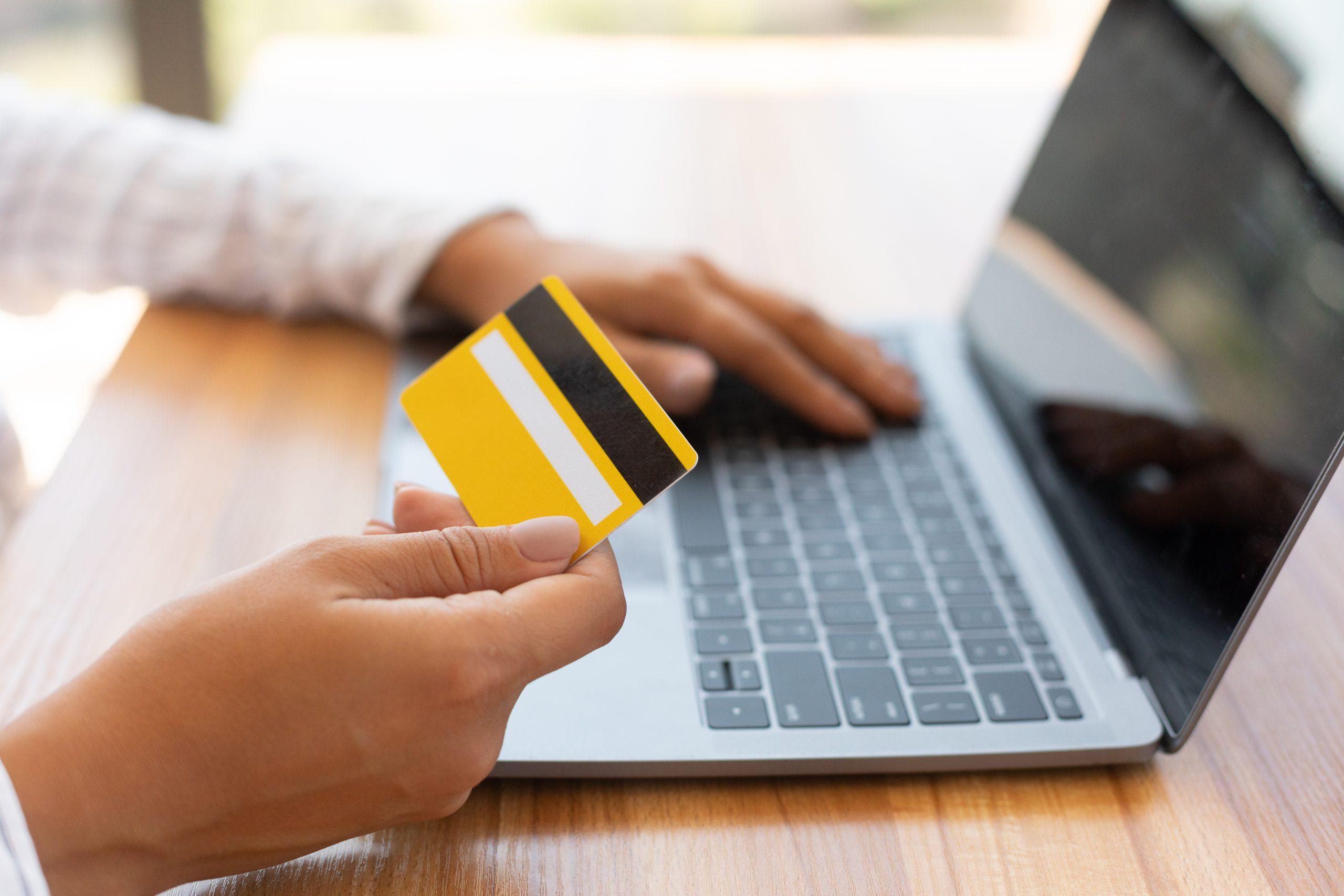 pessoa com cartão de crédito sem comprovação de renda na mão mexendo no notbook