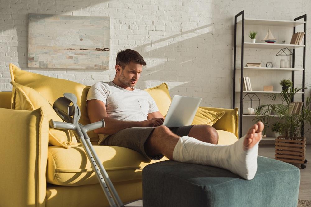 homem com perna engessada sentado no sofá mexendo no computador para solicitar o seguro DPVAT